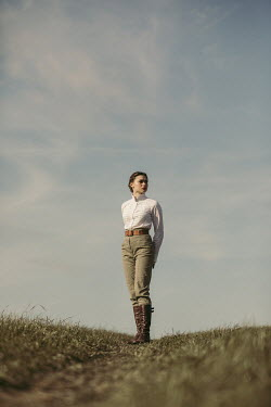 Magdalena Russocka young woman wearing white blouse, trousers and boots standing in field