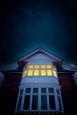 Nic Skerten LIGHT SHINING IN WINDOW OF HOUSE AT NIGHT