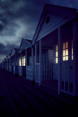 Nic Skerten ROW OF BEACH HUTS WITH LIGHTS AT NIGHT