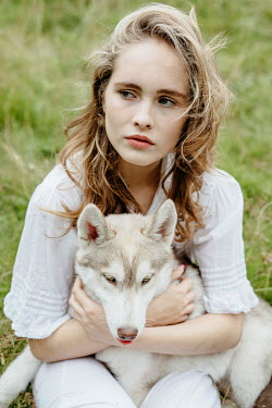 Shelley Richmond YOUNG GIRL SITTING HOLDING DOG OUTDOORS