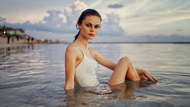 Georgy Chernyadyev WOMAN SITTING IN CALM SEA AT DUSK