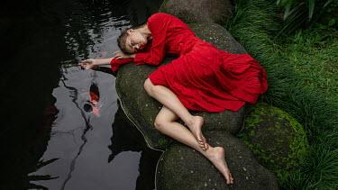 Georgy Chernyadyev WOMAN IN RED LYING BY FISH POND
