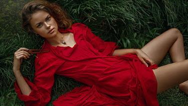 Georgy Chernyadyev WOMAN IN RED DRESS LYING ON GRASS