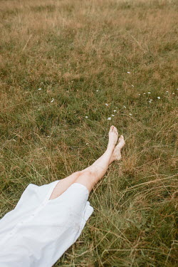 Shelley Richmond BAREFOOTED GIRL IN WHTE DRESS LYING IN FIELD