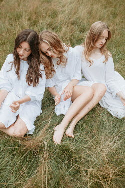 Shelley Richmond THREE GIRLS IN WHITE SITTING IN FIELD