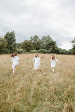 Shelley Richmond THREE WOMEN IN WHITE RUNNING IN FIELD