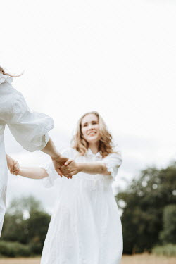 Shelley Richmond TWO GIRLS HOLDING HANDS AND DANCING IN COUNTRYSIDE