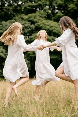 Shelley Richmond THREE GIRLS HOLDING HANDS AND DANCING IN COUNTRYSIDE