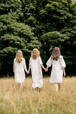 Shelley Richmond THREE GIRS WALKING HAND IN HAND IN COUNTRYSIDE