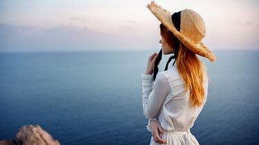 Georgy Chernyadyev WOMAN IN HAT ON CLIFF WATCHING SEA