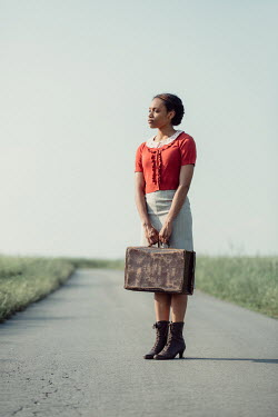 Magdalena Russocka retro african woman with suitcase standing on country road