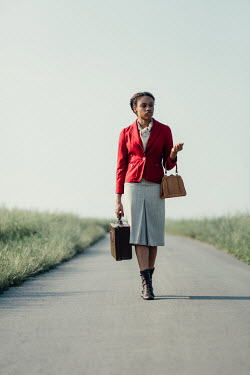 Magdalena Russocka retro african woman with suitcase walking on country road