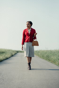 Magdalena Russocka retro african woman walking on country road