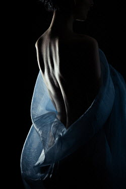 Magdalena Russocka nude woman wrapped in sheer shawl standing in shadow