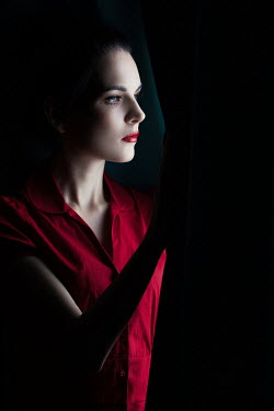 Magdalena Russocka woman peeking out from behind curtains