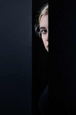 Magdalena Russocka woman peeking through gap in wall