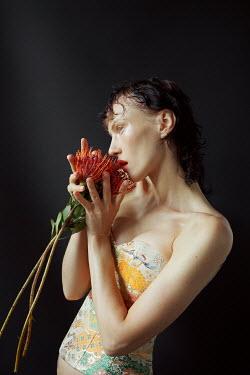 Marta Bevacqua WOMAN IN BODICE HOLDING RED FLOWER