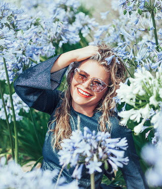 Eve North SMILING WOMAN WITH SUNGLASSES SITTING BY BLUE FLOWERS