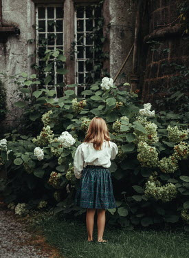 Eve North LITTLE GIRL BY EERIE BUILDING WITH FLOWERS