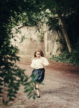 Eve North LITTLE GIRL RUNNING IN ROAD WITH STONE BUILDING