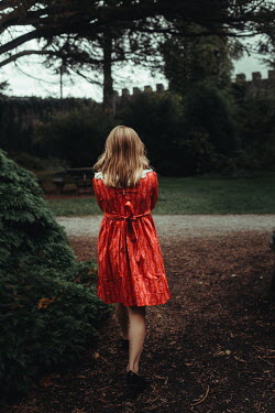 Eve North YOUNG GIRL IN RED WALKING IN CASTLE GARDEN