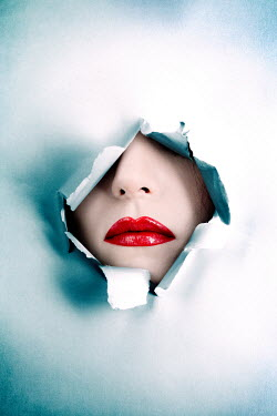 Magdalena Russocka womans lips through  hole in torn paper