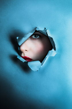 Magdalena Russocka womans face through  hole in torn paper