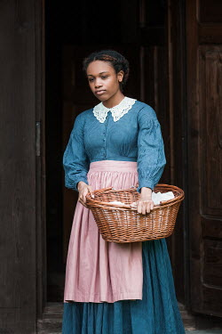 Magdalena Russocka historical african woman carrying basket standing on threshold of old cabin