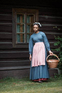 Magdalena Russocka historical african maid carrying basket walking by old cabin