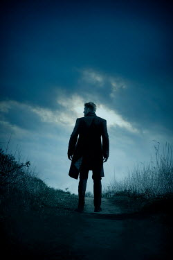 CollaborationJS MAN IN COAT STANDING ON COUNTRY PATH