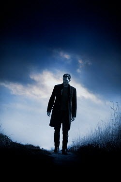 CollaborationJS MAN IN COAT ON COUNTRY PATH AT DUSK