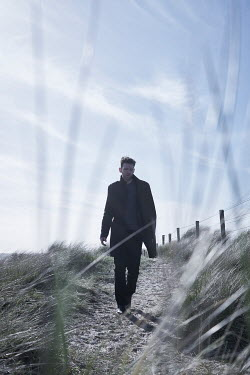CollaborationJS MAN IN COAT ON PATH IN SAND DUNES