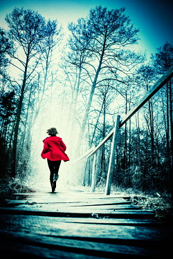 Magdalena Russocka woman running across wooden bridge in woods