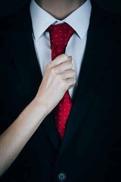 Magdalena Russocka woman's hand holding tie of man in suit