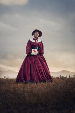 Magdalena Russocka historical woman holding letters standing in field