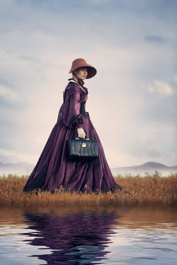 Magdalena Russocka historical woman carrying suitcase woman standing by river