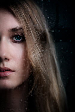 Ildiko Neer Half face of young woman behind wet glass