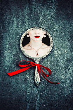 Magdalena Russocka woman's face with red lips reflected in old hand mirror