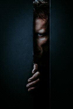 Magdalena Russocka close up of man peeking through gap in wall
