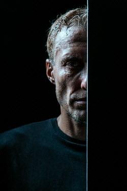 Magdalena Russocka close up of man looking from behind wall