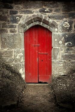 Miguel Sobreira Red Wooden Door in Stone Wall