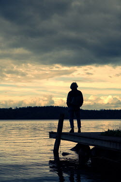Magdalena Russocka mature man standing on deck by lake at sunset