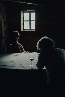 Magdalena Russocka mature couple sitting at table in shadowy room