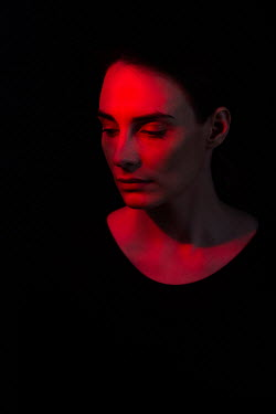 Magdalena Russocka close up of sad woman in shadow with red light