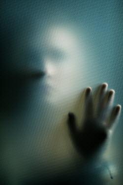 Ildiko Neer Shadowed woman behind patterned glass