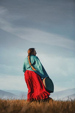 Magdalena Russocka historical woman carrying suitcase walking in field