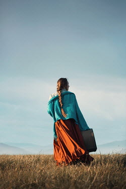 Magdalena Russocka historical woman carrying suitcase standing in field