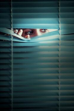 Ildiko Neer Young woman peeping behind blinds