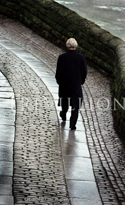 Clint Hughes MAN WALKING ON COBBLE STREET Men