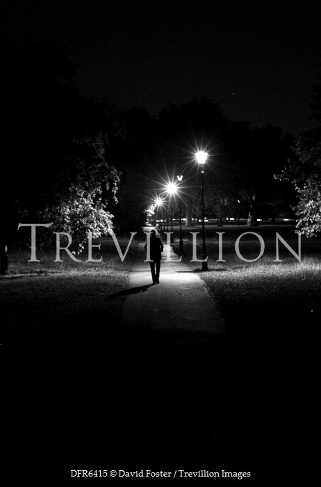 David Foster MAN WALKING THROUGH PARK AT NIGHT Men